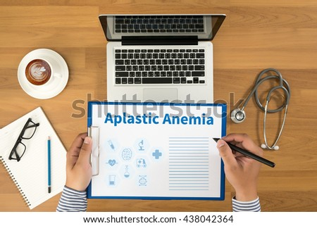 Aplastic Anemia Doctor writing medical records on a clipboard, medical equipment and desktop on background, top view, coffee - stock photo