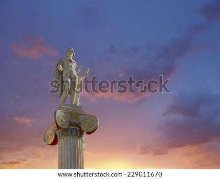 Apollo statue, the god of poetry and music under a fiery sky - stock photo