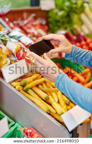 App in smartphone scanning barcode for price comparison in supermarket - stock photo