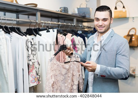 Apparel shop: male adult looking at expensive blouse price - stock photo