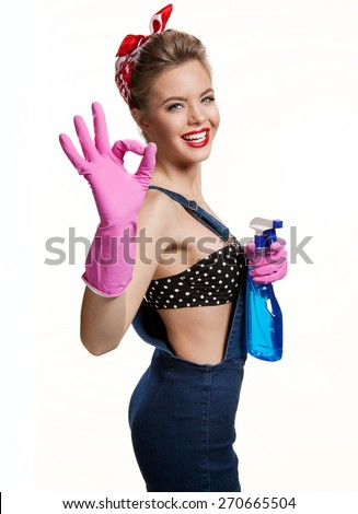 Appealing cleaning woman wearing pink rubber protective gloves holding spray Showing Us It's Okay / young beautiful American pin-up girl isolated on white background. Cleaning service concept - stock photo