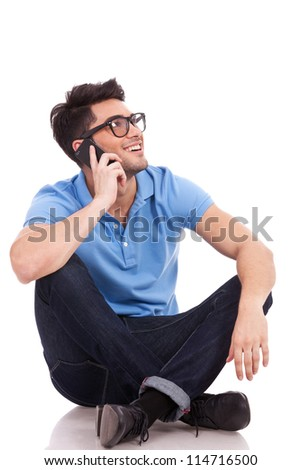 Appealing young casual man speaking over the phone and sitting with his legs crossed. He is looking somewhere up and smiling. - stock photo
