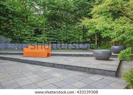 Appeltern, The Netherlands, July 22, 2015: The Gardens of Appeltern is the inspiration garden park in the Netherlands. In this picture a garden with a  striking orange sofa.