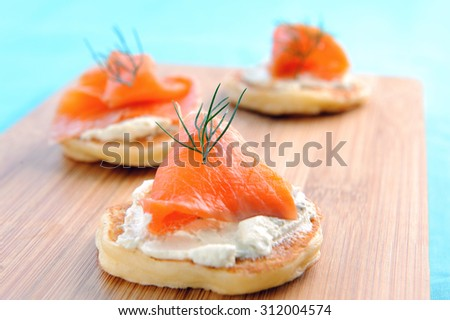Appetising smoked salmon and cream cheese blinis on a wooden platter  - stock photo