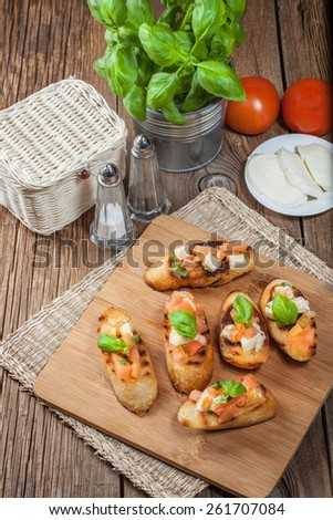 Appetizer bruschetta with roasted tomatoes, mozzarella cheese, garlic and basil. - stock photo