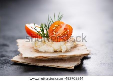 Appetizer canape with cherry tomato, cheese and dill on a small loaf of bread, closeup