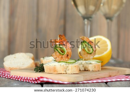 Appetizer canape with shrimp and cucumber on table close up - stock photo