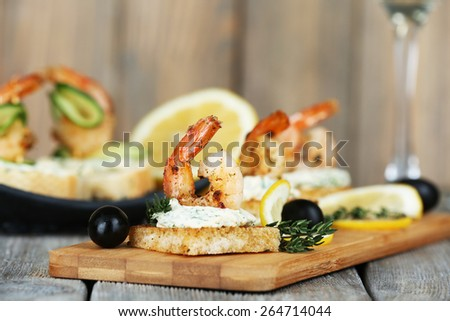 Appetizer canape with shrimp and olives on cutting board on table close up - stock photo