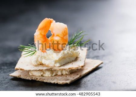 Appetizer canape with shrimp, cheese and dill on a small loaf of bread, closeup with copy space