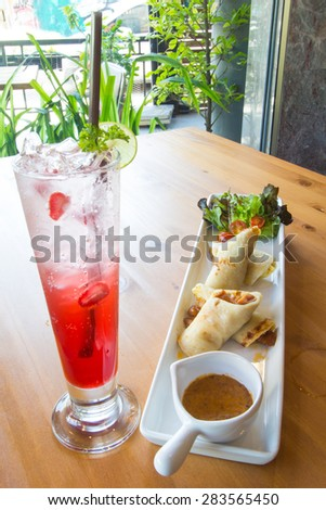 appetizer chicken wrap (wrap marinated chicken with peanut sauce) with red soda soft drink.