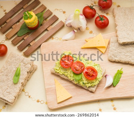 Appetizer. Crispbread with cream cheese (with garlic, parsley, basil, sorrel) and cherry tomatoes - stock photo
