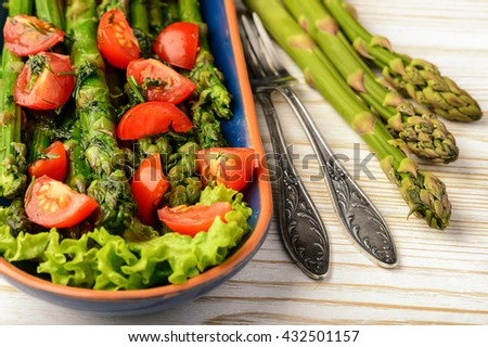 Appetizer - delicious vegetarian salad with green asparagus, tomatoes and vinaigrette dressing.