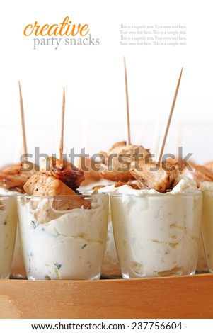 appetizer, fried chicken skewers with cheese dip in glasses, creative party snacks for cold buffet, sample text in the white background - stock photo