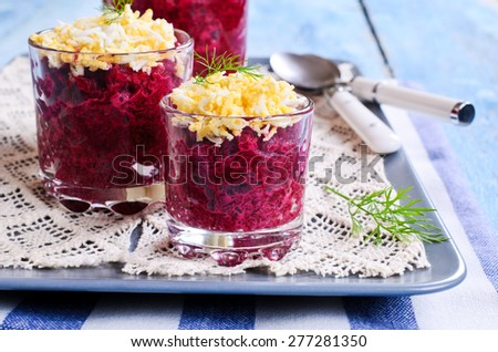 Appetizer of beets with eggs in portion cups - stock photo