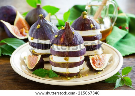 Appetizer of figs and brie cheese with honey. - stock photo