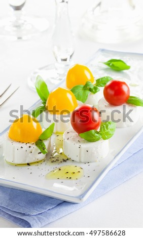 Appetizer of goat cheese with cherry tomatoes on rectangular serving plate with a blue napkin on a white background; vertical