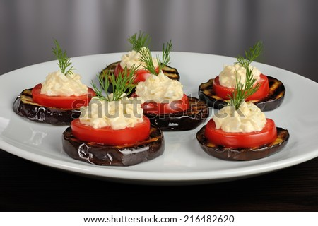 appetizer of grilled eggplant with tomato and spicy stuffing - stock photo