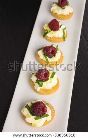 appetizer of mascarpone cream with lemon zest and cut mint leafs on a tapas cracker decorated with raspberry - stock photo