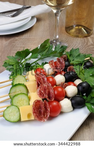 Appetizer of salami with mozzarella, olives, cherry tomatoes, cucumber and cheese on a skewer - stock photo