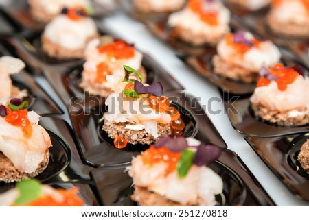 Appetizer of Salmon eggs, fish, and green herbs canapes - stock photo