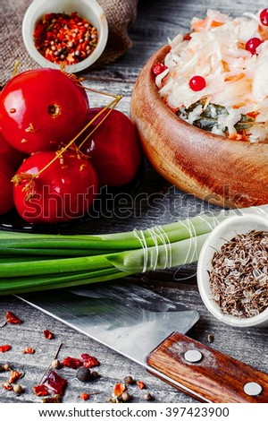 Appetizer of sauerkraut and pickled tomatoes in rustic style - stock photo