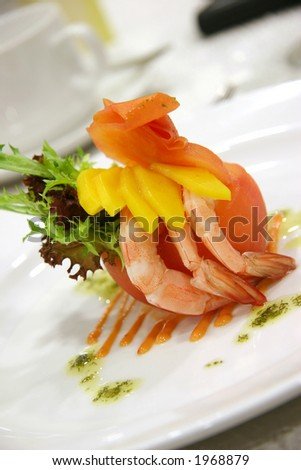Appetizer of shrimp and mango in a carved out tomato and a dash of different lettuce leaves