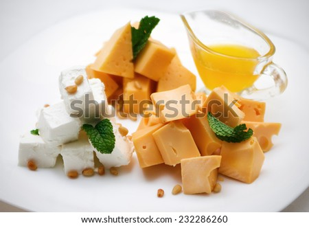 appetizer of three kinds of cheese and sauce on a white plate - stock photo