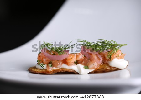 Appetizer on fried potato skins of red salted salmon, cream cheese, onions and dill at white plate. Closeup - stock photo