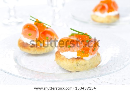 appetizer - potato bun with salted salmon, red caviar and green onion on a glass plate, closeup - stock photo