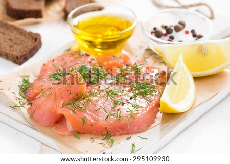 appetizer - salted salmon and bread on a wooden board, horizontal - stock photo