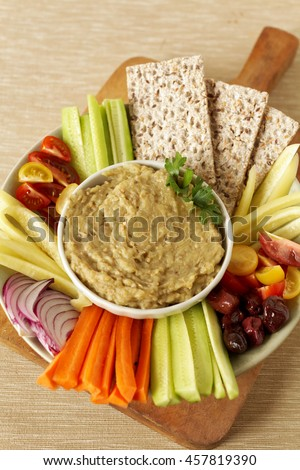 Appetizer vegetarian plate with aubergine salad dip, flat bread and raw vegetables