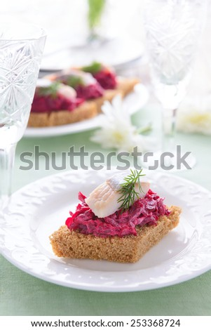Appetizer with beetroot pesto and slice of herring on festive table - stock photo