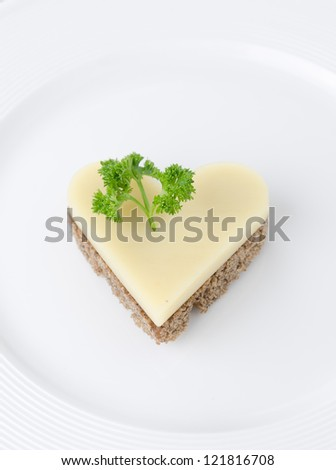 appetizer with bread and cheese in the shape of heart on a white plate - stock photo