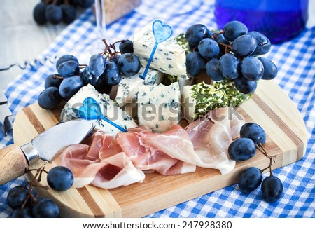 Appetizer with cheese, prosciutto and grape for wine - stock photo