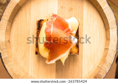 Appetizer with jamon and cheese on a wooden barrel. top view - stock photo