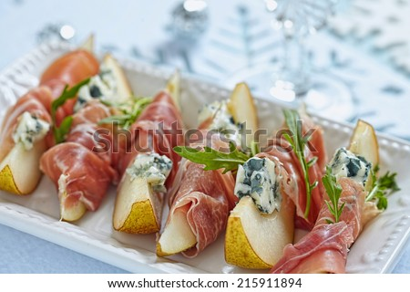 Appetizer with pear, prosciutto and blue cheese for holidays - stock photo