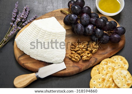 appetizer with ricotta. lavender, grapes, walnuts, olive oil and crackers. Knife for cheese - stock photo