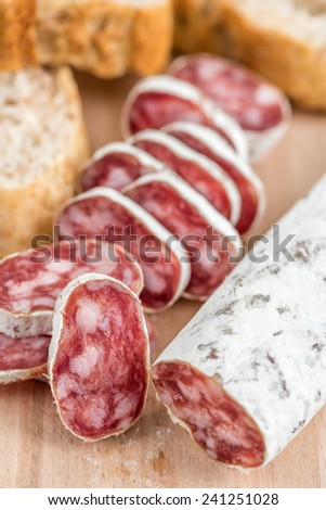Appetizer with slices of sausage (chorizo) and, bread - stock photo