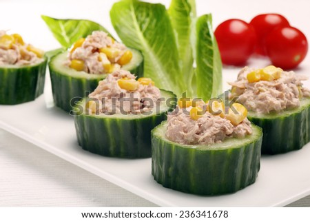 Appetizers cucumber with tuna and corn on white background - stock photo