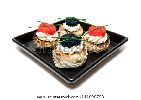 Appetizers: finger food - Black, rectangular plate with red and black caviar canapes (toasted bread, butter, caviar and chives), over white background. - stock photo