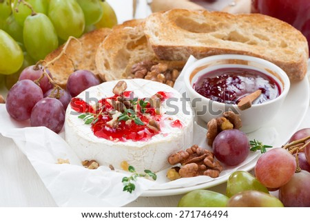 appetizers for wine - camembert with berry jam, toast and fruit on white table, close-up, horizontal - stock photo