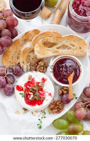 appetizers for wine - camembert with berry jam, toast and fruit on white table, vertical, top view, close-up - stock photo