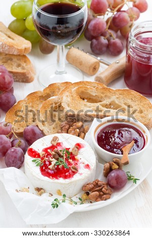 appetizers for wine - camembert with berry jam, toast and fruit, vertical, top view, close-up - stock photo