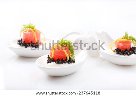 Appetizers in portion spoons of cream cheese, natural sturgeon black caviar, red salted salmon and dill on white table. Selective focus and place for text - stock photo