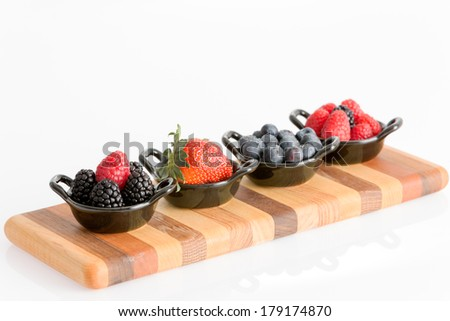 Appetizers of tasty fresh autumn berries in separate ceramic dishes with blueberries, strawberries, raspberries, and blackberries on a striped wooden board isolated on white with copyspace - stock photo