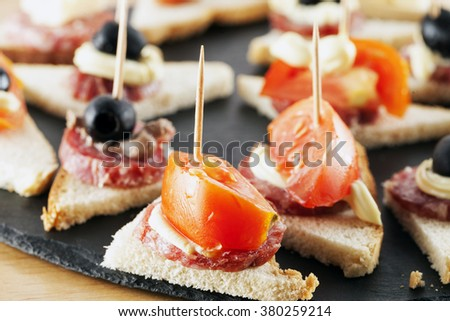 Appetizers over black stone plate, horizontal image - stock photo