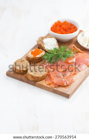 appetizers - salted salmon, red caviar, toast and cream cheese, vertical, top view - stock photo