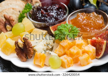 appetizers to the holiday - cheeses, fruits and jams, selective focus, closeup horizontal - stock photo