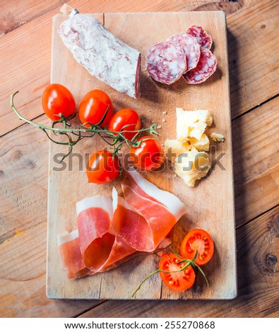 Appetizers - tomato, meat and cheese - on wooden board - stock photo