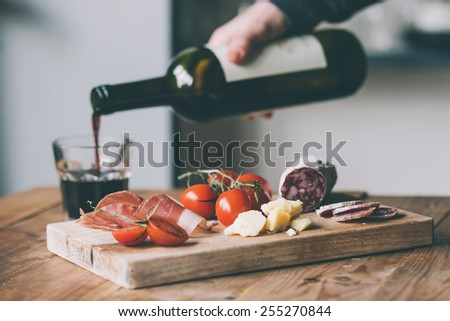 Appetizers - tomato, meat and cheese - on wooden board with bottle of wine and glass. Toned image - stock photo